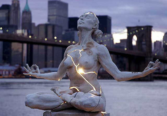 light shining out of cracked meditating woman sculpture